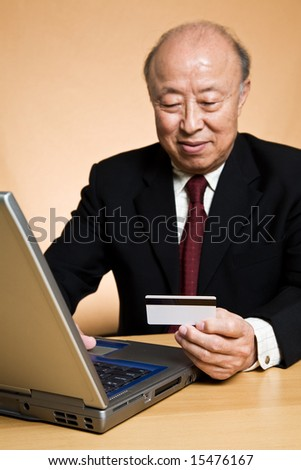 A shot of a senior asian businessman holding a credit card ready to make an online purchase (focus on the credit card)