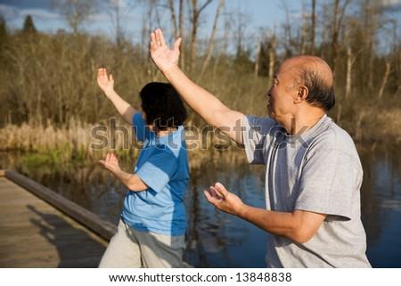 A shot of a senior asian couple doing tai-chi exercise