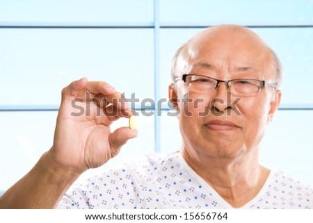 A shot of a senior asian man holding a pill
