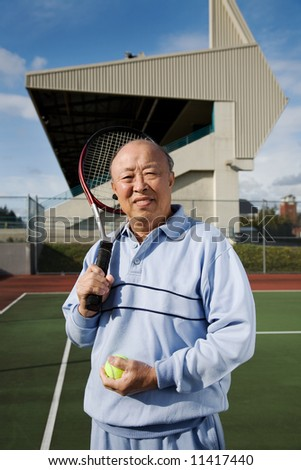 A shot of a senior asian man playing tennis - stock photo