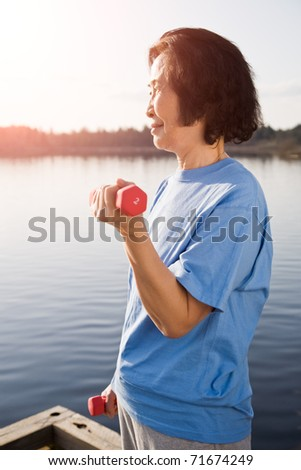 A shot of a senior asian woman exercising and lifting weights