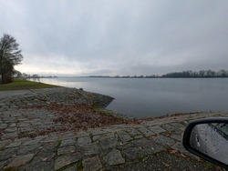 A shot of a still lake in rainy weather and a car mirror on the right