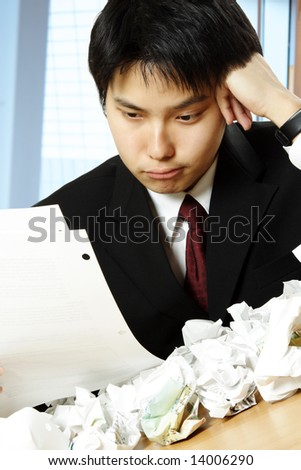 A shot of a stressed asian businessman working hard in the office with paper all over the table