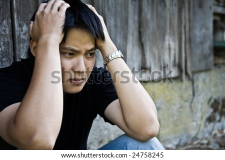 A shot of a stressed asian male outdoor