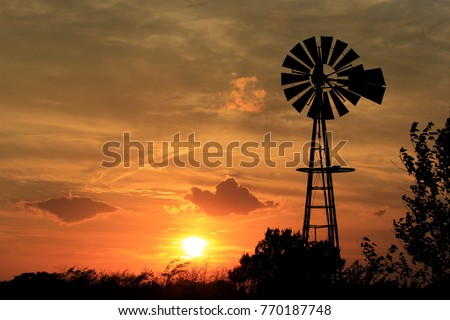 A shot of a Windmill Silhouette with a bright orange Sunset in the back ground  with tree silhouettes north of Hutchinson Kansas.