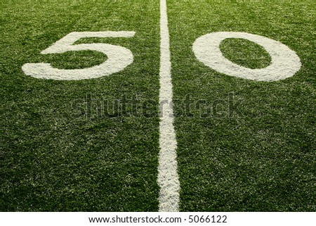 A shot of a 50 yardline at an american football field