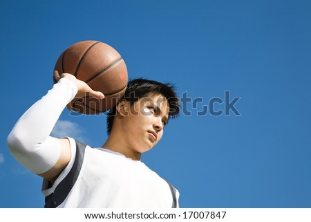 A shot of a young asian basketball player holding a basketball - stock photo