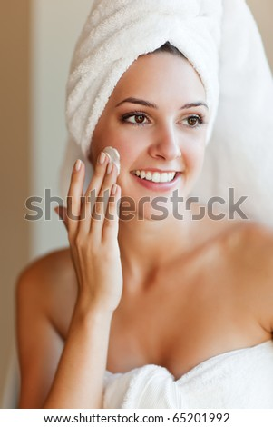 A shot of a young beautiful woman applying lotion to her face - stock photo