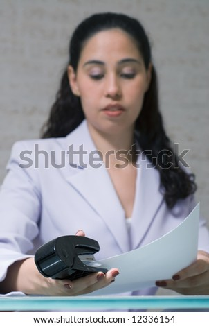 A shot of a young businesswoman stapling, with the focus on the stapler.