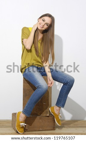A shot of a young girl isolated sitting in wooden cube
