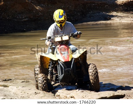 A shot of a young man running some muddy trails on his ATV.
