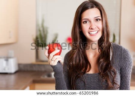 A shot of a young woman holding an apple