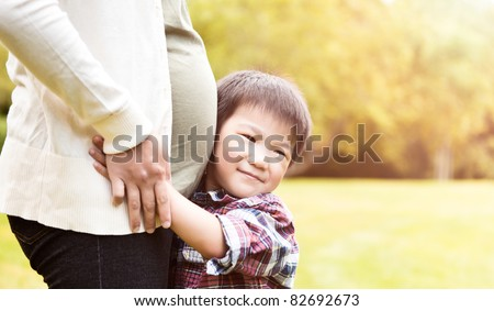 A shot of an Asian boy kissing the belly of his pregnant mother - stock photo