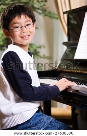 A shot of an asian boy playing piano