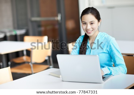 A shot of an Asian college student working on her laptop on campus