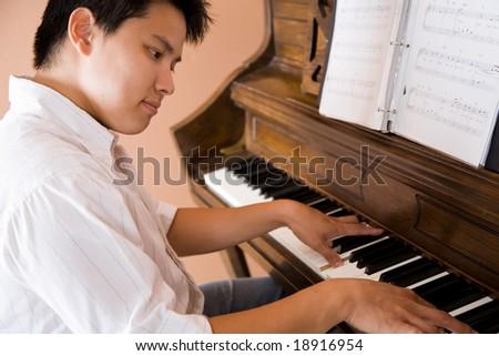 A shot of an asian man playing piano