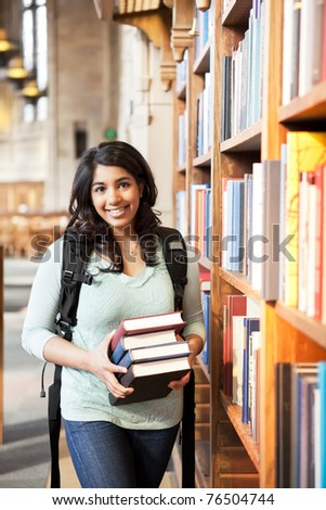 A shot of an asian student holding books at the library
