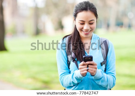 A shot of an Asian student texting on the phone