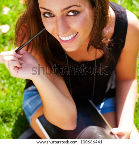 A shot of an caucasian student studying on campus lawn - stock photo
