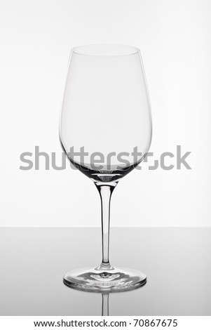 A shot of an empty wine glass with reflection on white background