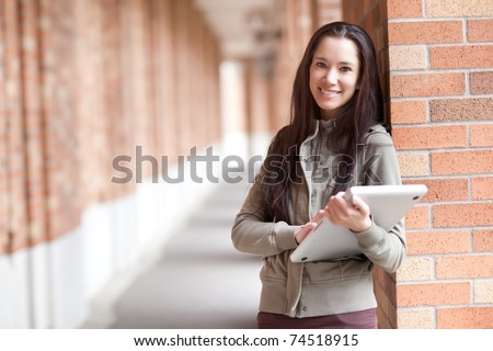 A shot of an ethnic college student carrying a laptop on campus