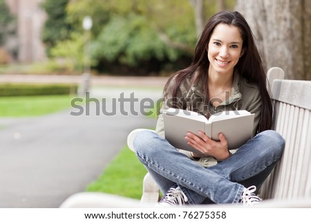 A shot of an ethnic college student studying on campus - stock photo
