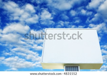 A shot of blank billboard against a cloudy blue sky