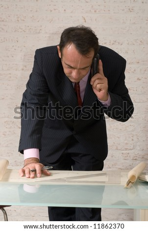 A shot of businessman, standing and talking on cellphone, looking at set of plans.