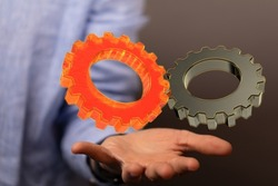 A shot of 3d models of orange and gray cogwheels over a human hand