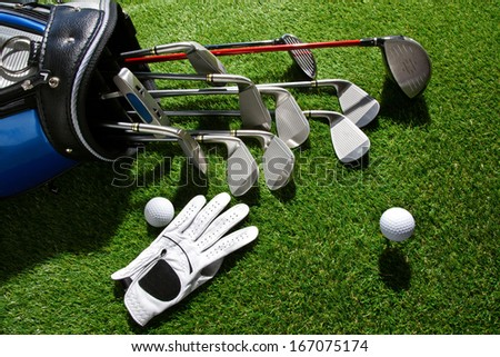 A shot of Golf glove,ball and clubs in bag