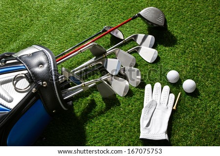 A shot of Golf glove,balls,tee and clubs in bag