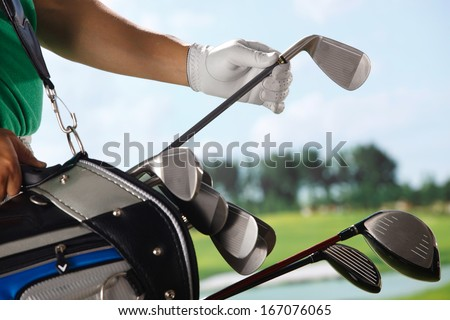 A shot of Golf player removing golf club from bag