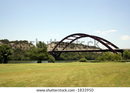 A shot of the Austin 360 Bridge on a clear calm day.  This is a very pretty picture of the bridge and a great symbol of Austin, Texas.