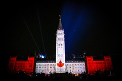 A shot of the parliament center block at Ottawa, Ontario, Canada at night when there is a light show going on displaying the Canadian flag