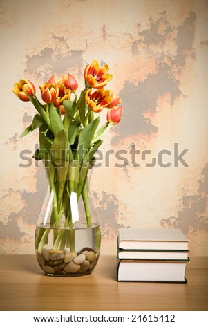 A shot of tulips in a vase and books, home decoration concept