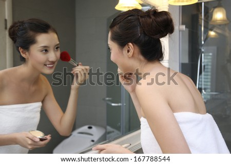 A shot of Young woman making-up in bathroom
