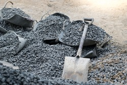 A shovel is placed on a pile of rocks with a bucket.