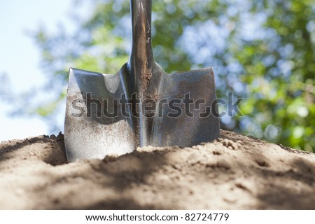 A shovel is stuck in a pile of dirt with bokeh in the background.