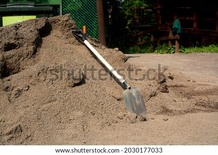 A shovel lying on a pile of sand. Black shovel with a wooden handle and a special handle. Outdoor building materials. Foto d'archivio ©