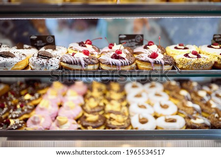 A show case full of delicious donuts of irresistible appearance in a candy shop. Pastry, dessert, sweet Stock photo ©