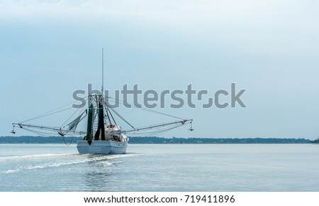 A Shrimp Boat Trawler Heading to Sea for a Day of Fishing in Savannah Georgia #719411896