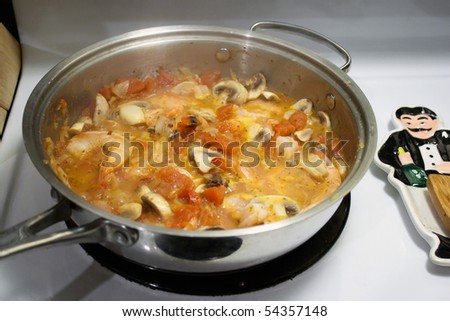 A shrimp scampi dish in a light wine sauce being prepared in a skillet on the stove.  Shallow depth of field.