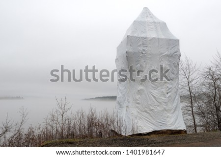 A shrink wrapped lighthouse on a foggy, overcast day in the spring. Tress and bushed with no leaves nearby, Islands in the distance.