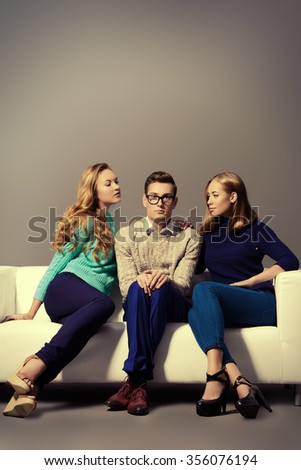 A shy young man sitting on the couch with two attractive girls. Beauty, fashion.