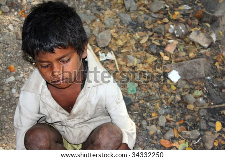A sick beggar boy sitting hopelessly in his poverty conditions in India.