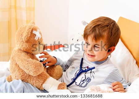 a sick child examined teddy with stethoscope