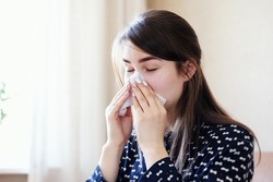 A sick, exhausted woman blows a runny nose into a napkin because she fell ill with the flu or a cold - A girl is sick with seasonal allergies and blows her nose in a handkerchief with a napkin