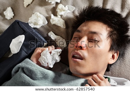 A sick male sleeping with lots of used tissue around him