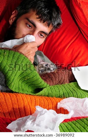 A sick man at home, laying down with his cat and tissue paper.