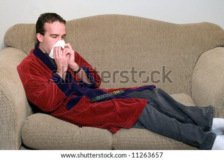 A sick man lying on a couch, blowing his nose